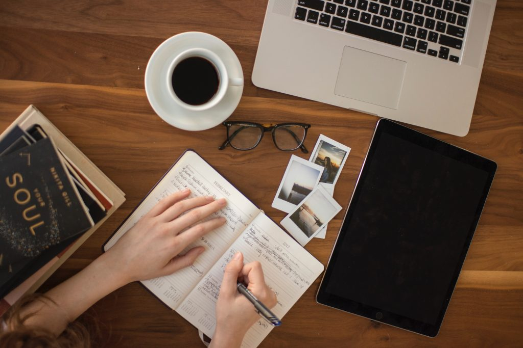 A woman's hand writing in a journal over a desk with a notebook, glasses, a cup of coffee, some books and pictures.